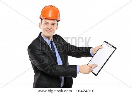 Young Foreman Wearing Helmet And Pointing On A Clipboard