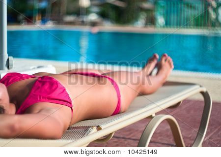 A Beautiful Young Unrecognizable Girl In A Bikini Lying On A Beach Bed Near The Hotel Swimming Pool
