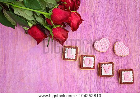 Red Roses And Pink Cookies In Shape Of Love Word, On Pink Wooden Background, Top View