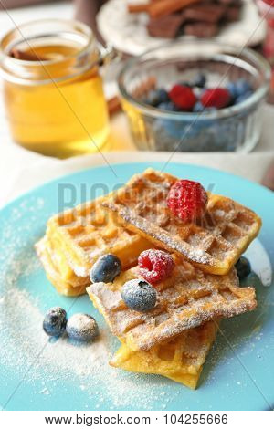Sweet homemade waffles with forest berries on plate, on light background