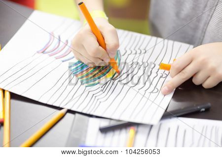 Child paints a felt pen drawing of hand