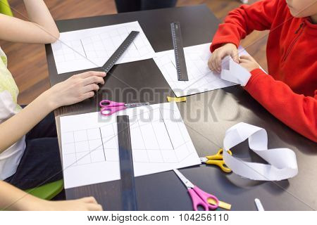 children make crafts out of paper on the table