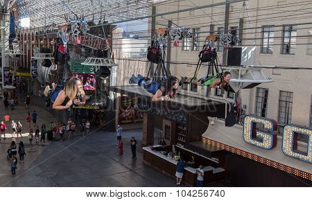 Zip line riders fly above Freemont Street