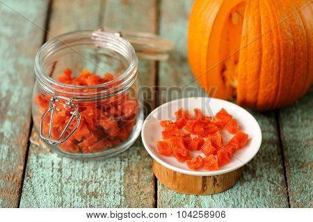 Homemade Candied Pumpkin Pieces In Glass Jar And White Plate With Whole Cut Pumpkin On Old Wooden Ta