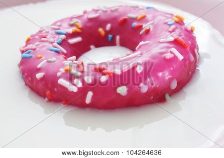 closeup of a donut coated with a pink frosting and sprinkles of different colors being soaked in milk