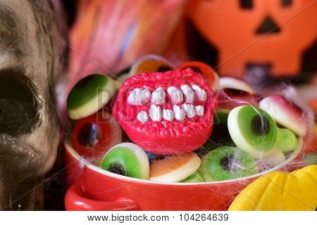closeup of a red bowl with different Halloween candies, and some scary ornaments, such as a skull or a carved pumpkin