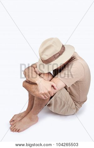 Man sitting hiding his face under a hat
