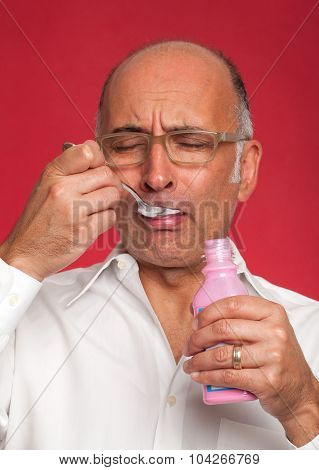 Man with an expression of disgust taking medicine