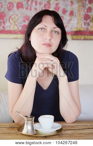 Girl drinks coffee in a cafe