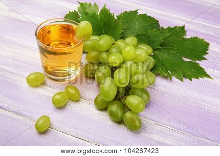 Glass of grape juice on wooden background