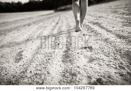 Footprints On The Sand With Walking Girl On Background