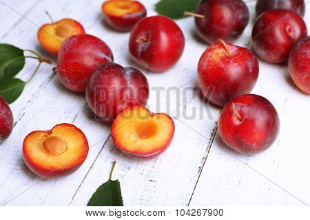 Ripe plums on white wooden background