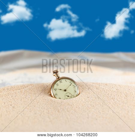 Vintage pocket watch semi buried in the sand