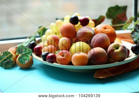 Heap of fresh fruits on windowsill