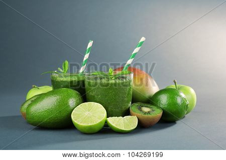 Green healthy juice with fruits and mint on gray background