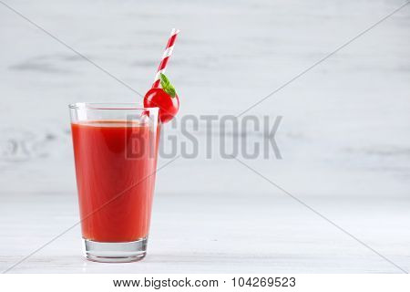 Glass of tomato juice with vegetable on wooden background
