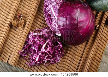 Red cabbage and onion on wooden table closeup