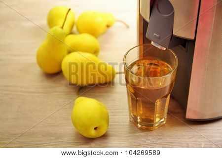 Juicer and pear juice on kitchen table