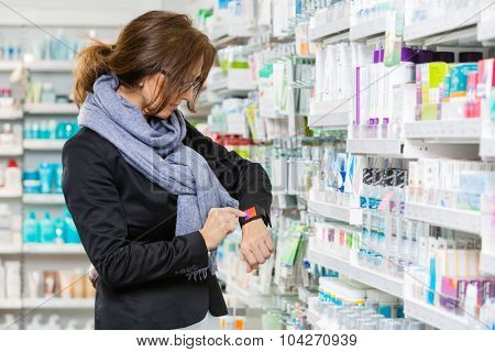 Mid adult female consumer using smartwatch in pharmacy