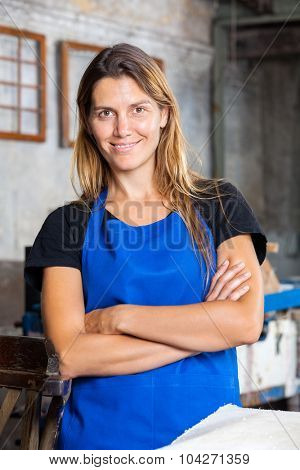Portrait of confident female worker with arms crossed smiling in paper factory