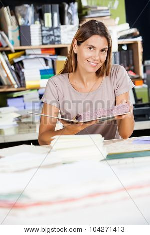 Portrait of smiling mid adult female worker holding spiral book in factory