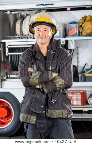 Portrait of mature male firefighter standing arms crossed against firetruck at station