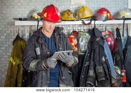 Mature fireman in uniform using digital tablet at fire station