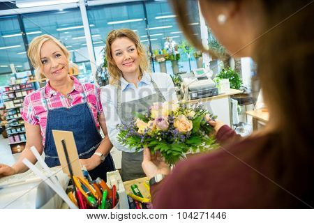 Happy florists selling rose bouquet to female customer in flower shop