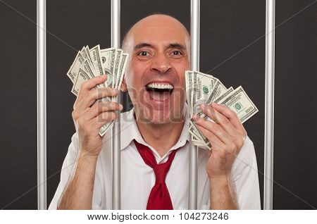 Man in jail laughing with money in his hands