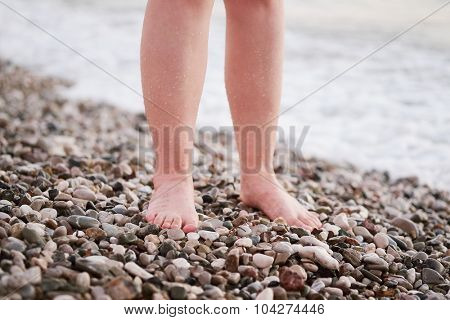 Legs of a girl, stands on a pebble