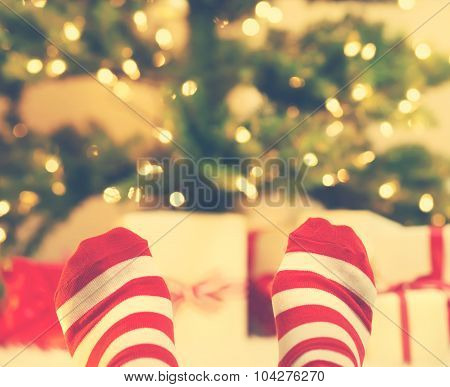 Feet With Striped Socks With Christmas Gift Boxes