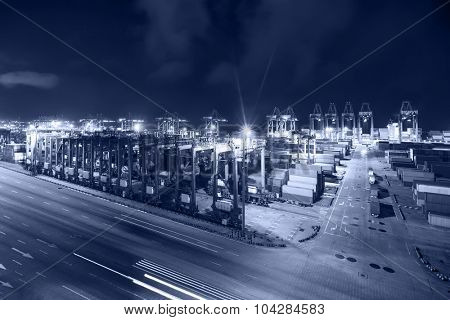 containers and cranes at the harbor at night
