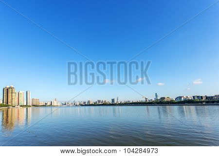 skyscrapers by the river bank under blue sky