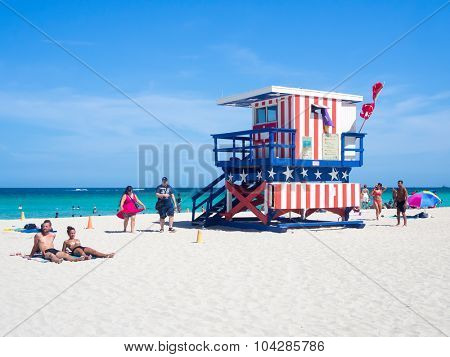 MIAMI,USA - AUGUST 8,2015: Summer day at South Beach in Miami next to the famous lifeguard tower decorated with the colors of the american flag
