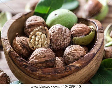 Walnuts in the wooden bowl on the table.