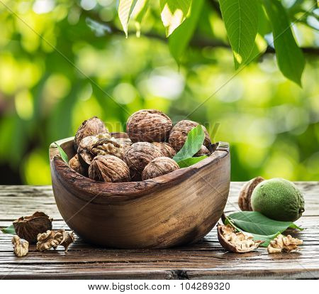 Walnuts in the wooden bowl on the table. The bright nature background.