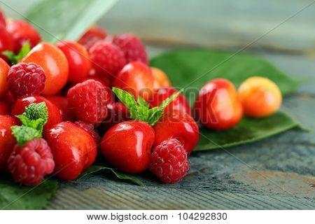 Sweet cherries, raspberries with green leaves on wooden background