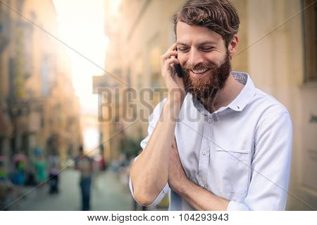 Smiling man doing a phone call