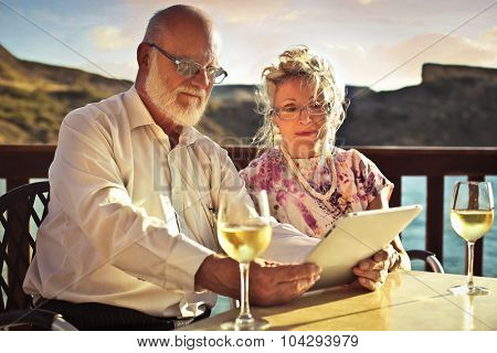 Husband and wife sitting at a table with a glass of wine