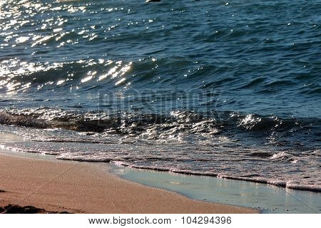 Sea shore at night, light waves and velvety sand