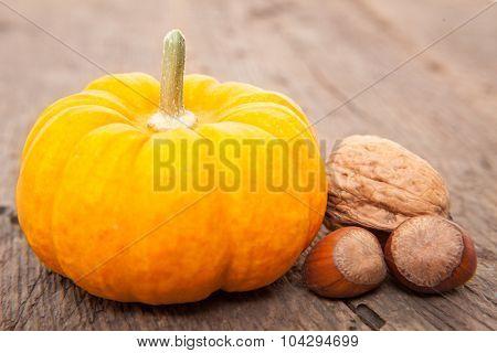 Pumpkin next to walnuts and hazelnuts