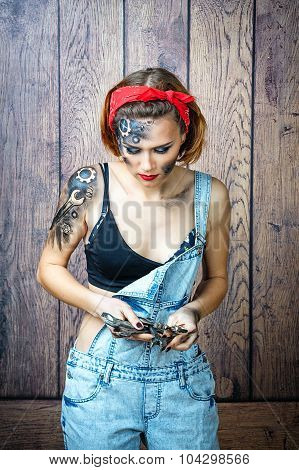 Girl Mechanic With Face Art Selects Tools For Job.