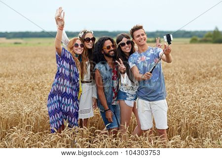 nature, summer, youth culture, technology and people concept - smiling young hippie friends in sunglasses taking picture by smartphone on selfie stick and showing peace gesture on cereal field