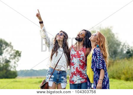nature, summer, youth culture and people concept - smiling young hippie friends in sunglasses pointing finger up outdoors