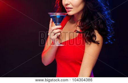people, holidays, party, alcohol and leisure concept - close up of beautiful sexy woman in red dress drinking cocktail at night club