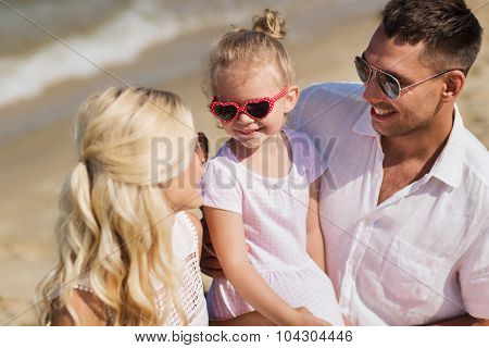 family, vacation, adoption and people concept - happy man, woman and little girl in sunglasses talking on summer beach