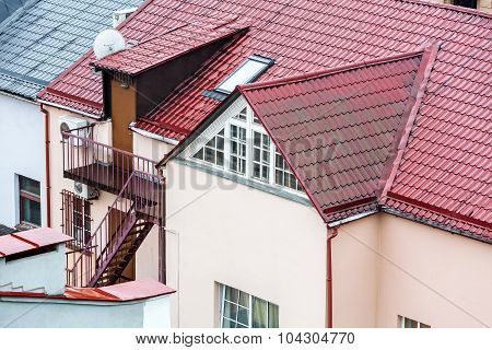 Wet Tiled Red Roof With Attic Windows