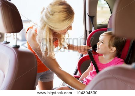 family, transport, safety, road trip and people concept - happy mother fastening child with car seat belt