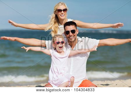 family, vacation, adoption and people concept - happy man, woman and little girl in sunglasses having fun on summer beach