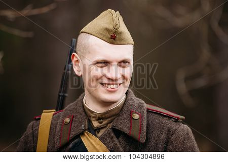 Young smiling unidentified re-enactor dressed as Soviet soldier